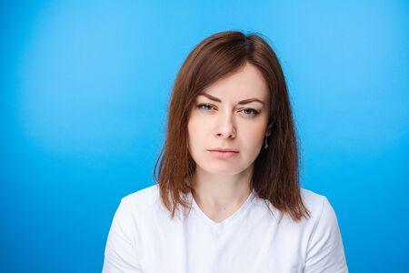 Suspicious woman looking at camera. light blue background