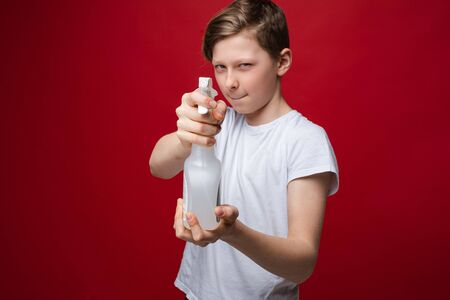 Portrait of fearless teenage male holding spray disinfectant bottle bacterial protection Banque d'images