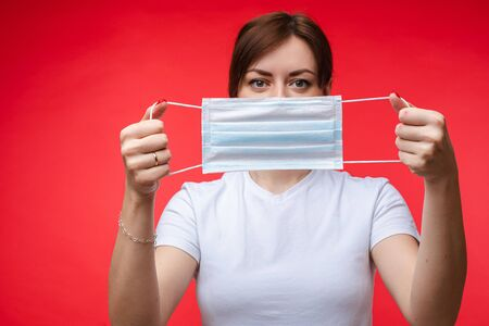 Woman with aseptic mask in hands. Isolate on red. Banque d'images