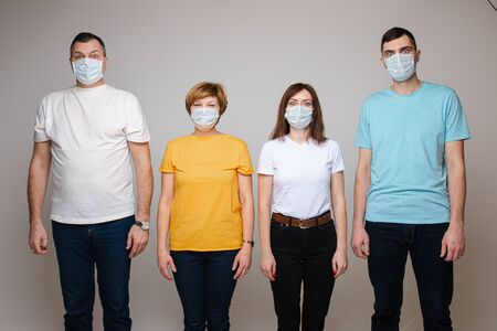 A family of four stands with masks on their faces and dont hold hands, isolated on grey background