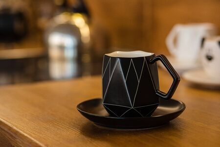 Black cup with white lines on the little plate in the brown kitchen