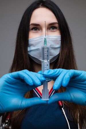 Beautiful woman doctor in white medical clothes, mask, blue gloves and phonendoscope on her shoulders isolated on blue background 写真素材