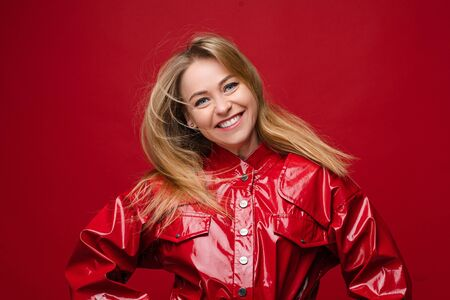 Pretty girl in red leather shirt smiling at camera.