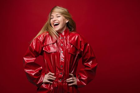 Laughing woman in red leather overall having fun.