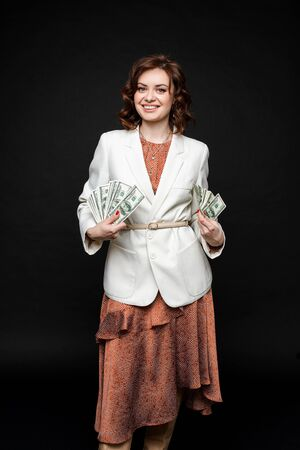 Cute young girl shows a lot of money in the hands, picture isolated on black background