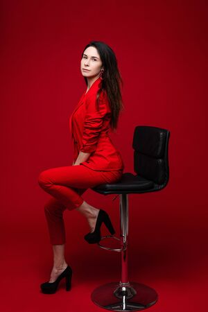 Attractive woman poses for the office magazine and sits on the chair, picture isolated on red background