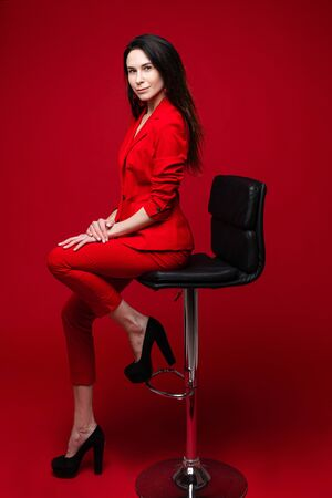 Charming caucasian female with long dark straight hair in red office suit, black shoes sits on black chair aand poses for the camera