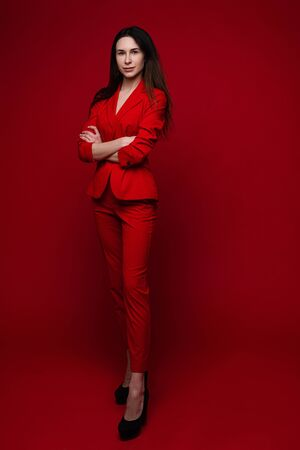 Charming woman poses for the office magazine, picture isolated on red background