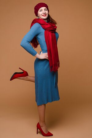 Portrait of beautiful caucasian female with medium dark hair in blue dress, red hat and red scarf