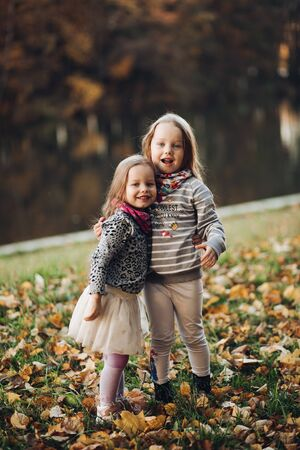 Two beautiful little sisters stand and hugs each other Zdjęcie Seryjne