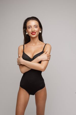 Cheerful woman in swimsuit shows a lot of poses for the camera, picture isolated on white background