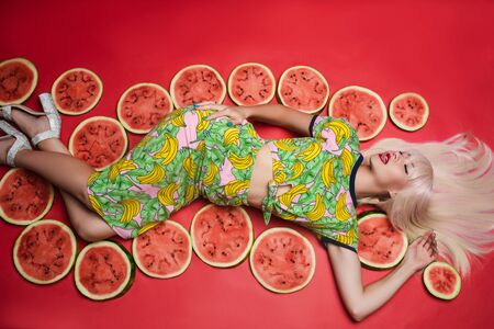 Sexy beautiful young woman lying on floor posing for photo shooting surrounded by watermelon Stock fotó