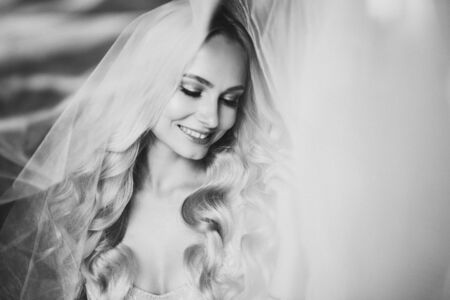 Monochrome portrait of sensuality and charming smiling bride.