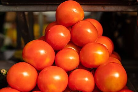 A lot of tomatoes lie on top of each other in the shape of a pyramid in the sunlight 版權商用圖片