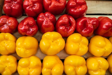 Beautiful photo of yellow and red red peppers isolated on wooden background 版權商用圖片