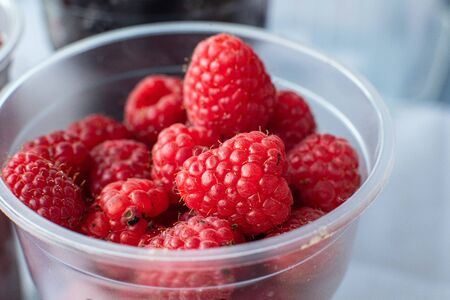 Picture of sweet, tasty, red and fresh raspberries are in the small plastic cup