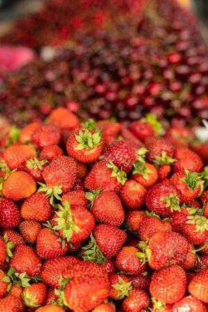 Picture of sweet, tasty, red and fresh strawberries and cherries lying in wooden boxes in the store