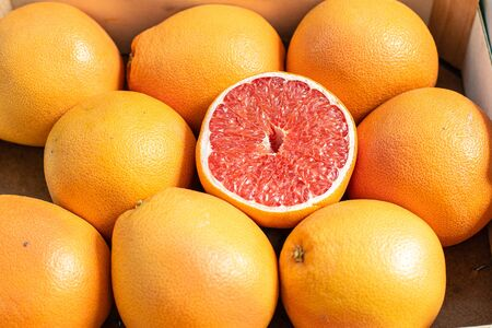 Close up picture with a lot of fresh orange and red grapefruits in the sunshine.