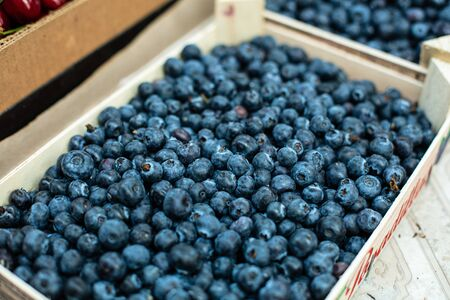 Picture of sweet, tasty and fresh blueberries lying in wooden boxes in the store.