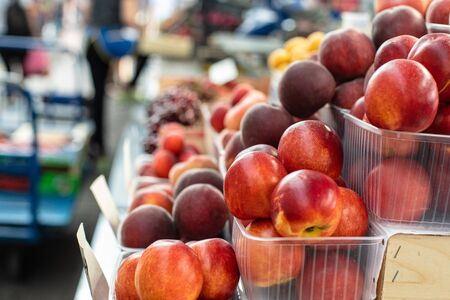 Picture of sweet, tasty and fresh peaches lying in small plastic boxes in the store.