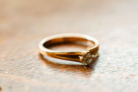 Small, neat diamond engagement ring on the wooden table