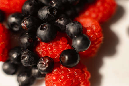 Many juicy fresh ripe raspberry berries lie in a white ceramic plate on the table under bright sunlight 版權商用圖片