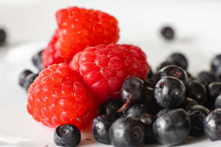 Many juicy fresh ripe red raspberry berries with blackberries isolated on white background 版權商用圖片