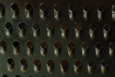 Ordinary metal kitchen grater with oval holes on it, picture background
