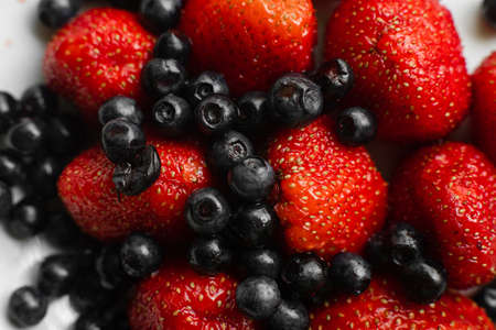 Close up of mix of fresh berries on white background