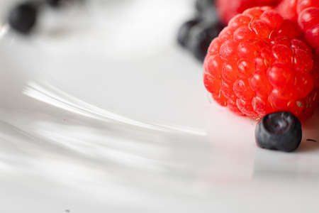 Two different kinds on berries on white plate