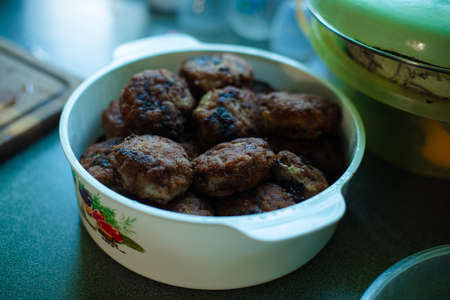 Plenty of ready-made fried meatballs lie in a large white aluminum pan on the table