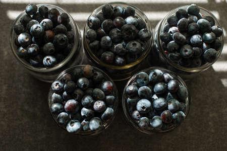 Many large beautiful juicy fresh blueberries lie in glass jars