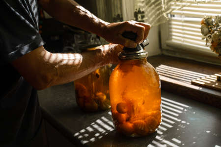 A woman rolls a compote in a large jar under the sun in summer at home in the village
