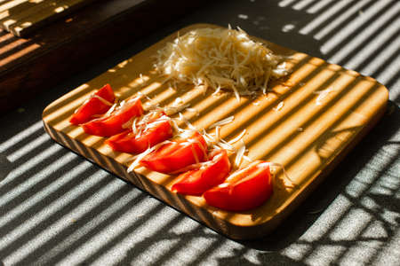 A small pile of grated fresh cheese and red tomatoes lies on a wooden board in the kitchen 版權商用圖片