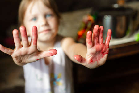 Little kid showing her hands painted in bright colors