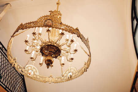 A large, beautiful chandelier with many expensive stones hangs on the ceiling in a church