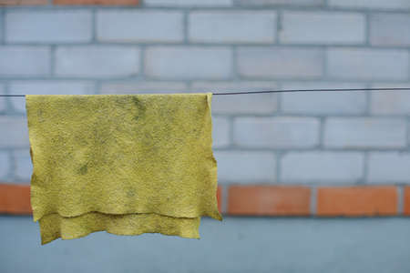 An old yellow rag for cleaning dries up in the street. A rag hangs on a rope