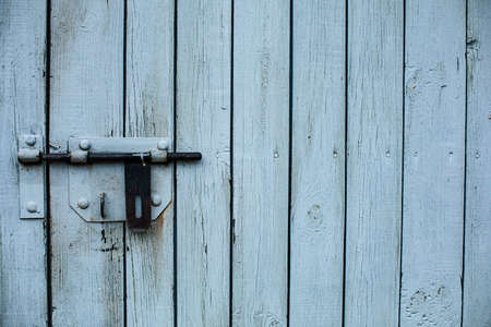 A wooden fence, a door. White boards
