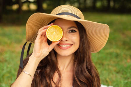 Portrait of a young beautiful girl with even white teeth, a beautiful smile in a straw hat holds a lemon next to her face