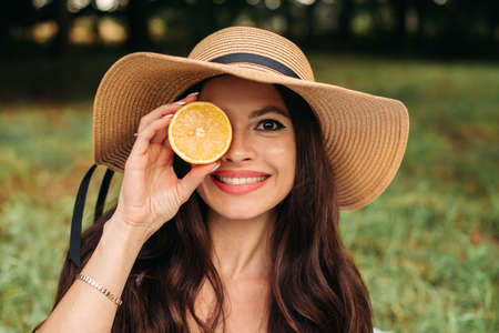 Smiling girl in hat with orange in hand. 版權商用圖片