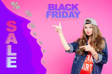 Young beautiful modern girl advertises discounts in the store, informs customers about Black Friday