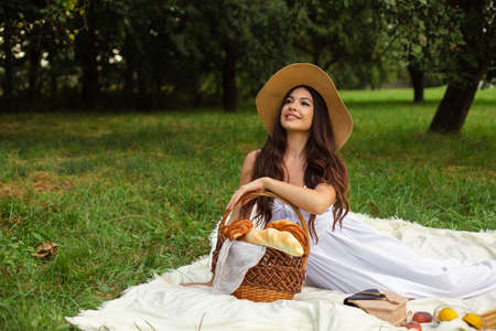 Portrait of a young beautiful girl with even white teeth, a beautiful smile in a straw hat have a picnic in the garden 版權商用圖片