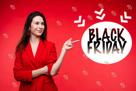A portrait of a young girl points to a sign that says Black Friday and recommends it, picture isolated on red background 版權商用圖片