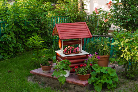 A small decorative well with a lot of color near it in the village yard