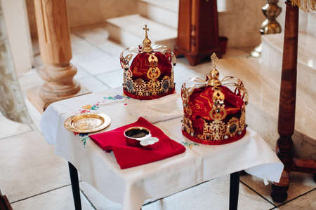 Two beautiful crowns with gold and red cloth stand on a table in the church before the baptism of the baby Archivio Fotografico