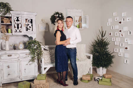 Picture of a young handsome guy with short dark hair hugging his wife with long hair next to a Christmas tree Stok Fotoğraf