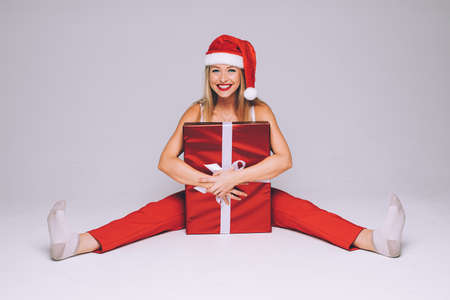 Girl hugging Christmas present in studio.