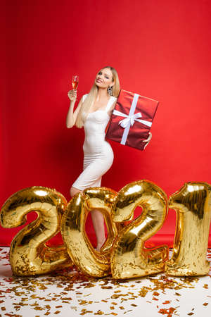 pretty woman in elegant white dress near big gold baloons with numbers 2021 and holds a big christmas gift and champagne