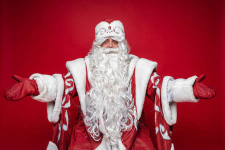 Welcome gesture of Santa Claus on red studio background, xmas and new year advertising photography Stok Fotoğraf