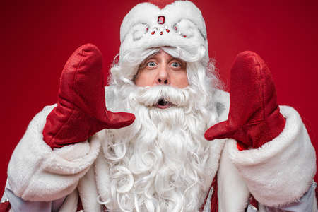 Santa Claus show size of something by hands in mittens with surprized face on red background, holiday emotions concept